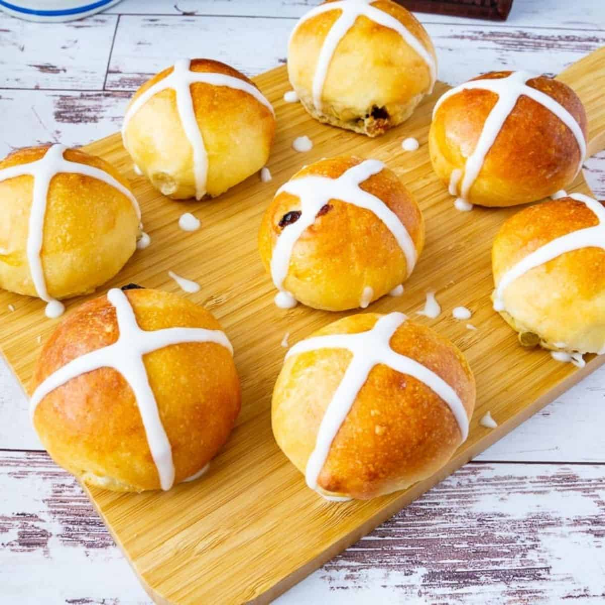 Hot cross buns on a wooden board.
