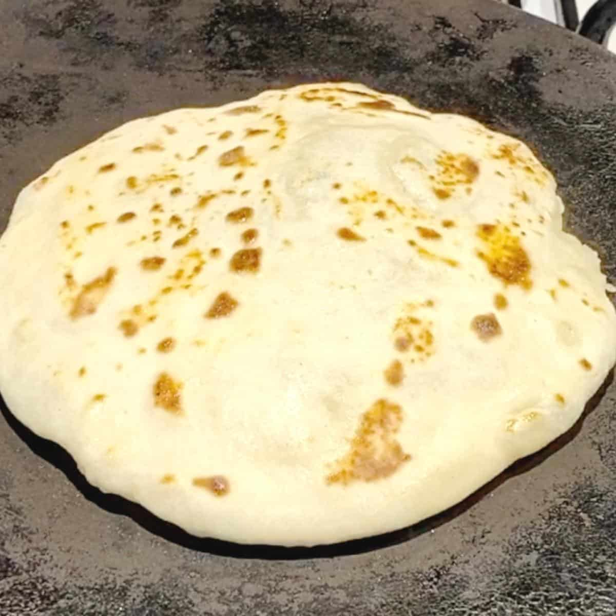 A skillet cooking flatbread filling with mashed potato.