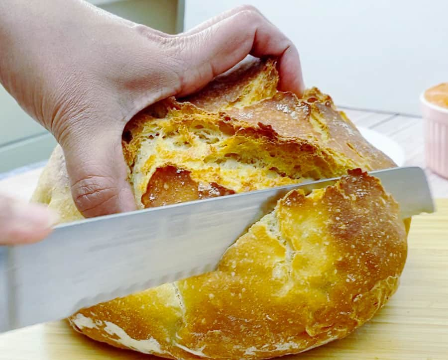 A person slicing a loaf of crusty bread.