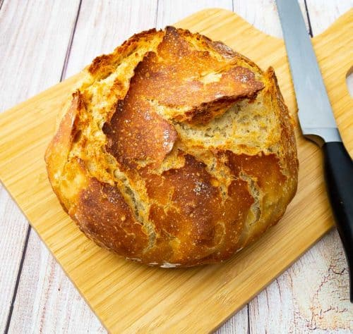A crusty loaf of bread on a wooden cutting board.