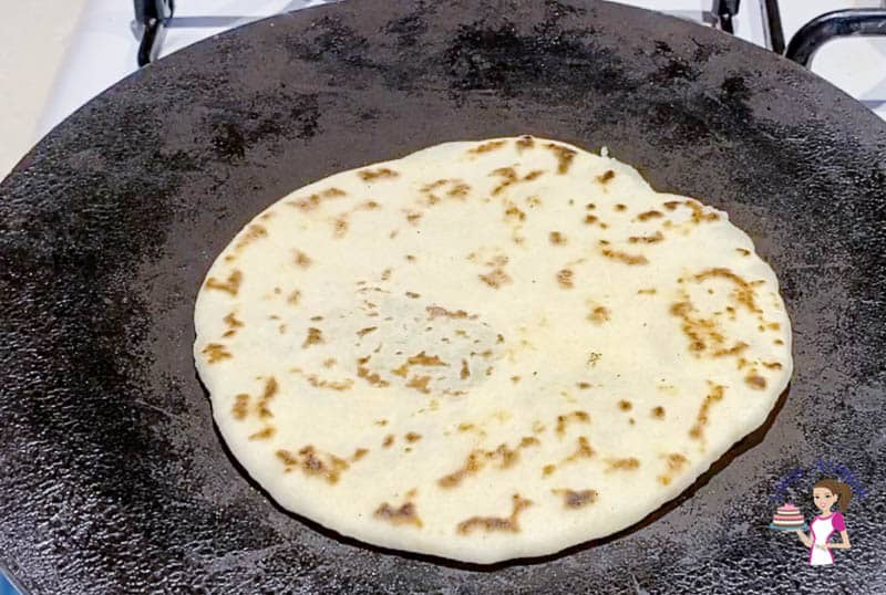 Cooking the potato stuffed flatbread on a cast iron skillet