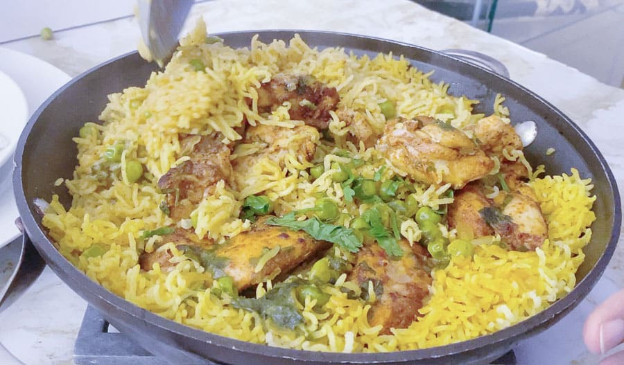 A close up of a skillet with chicken and rice.