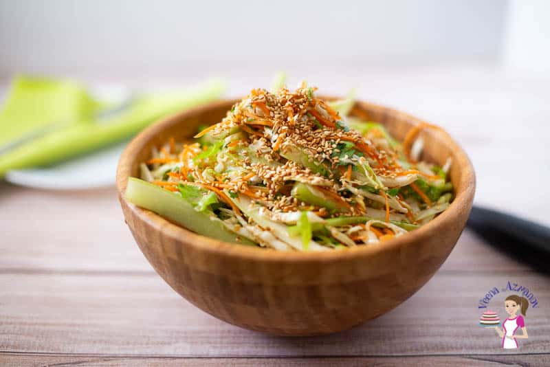 A bowl of Asian salad on a table.