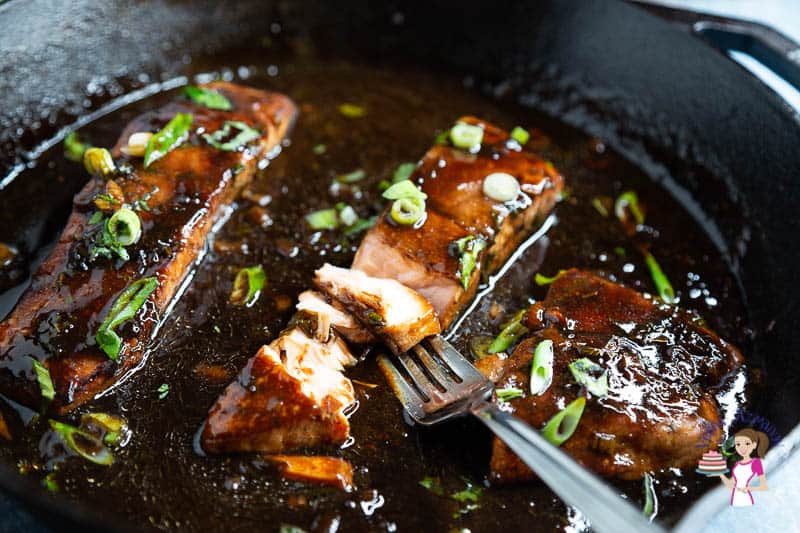 Salmon glazed with balsamic and honey in a cast iron pan.
