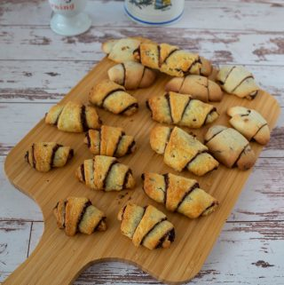 Several Chocolate rugelach pastry on a wooden tray.
