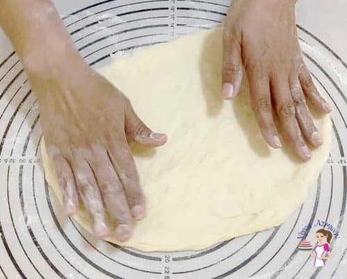 Roll the pizza dough to make a classic Margherita