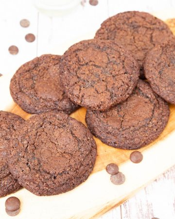 Fudgy chocolate cookies on a wooden board.
