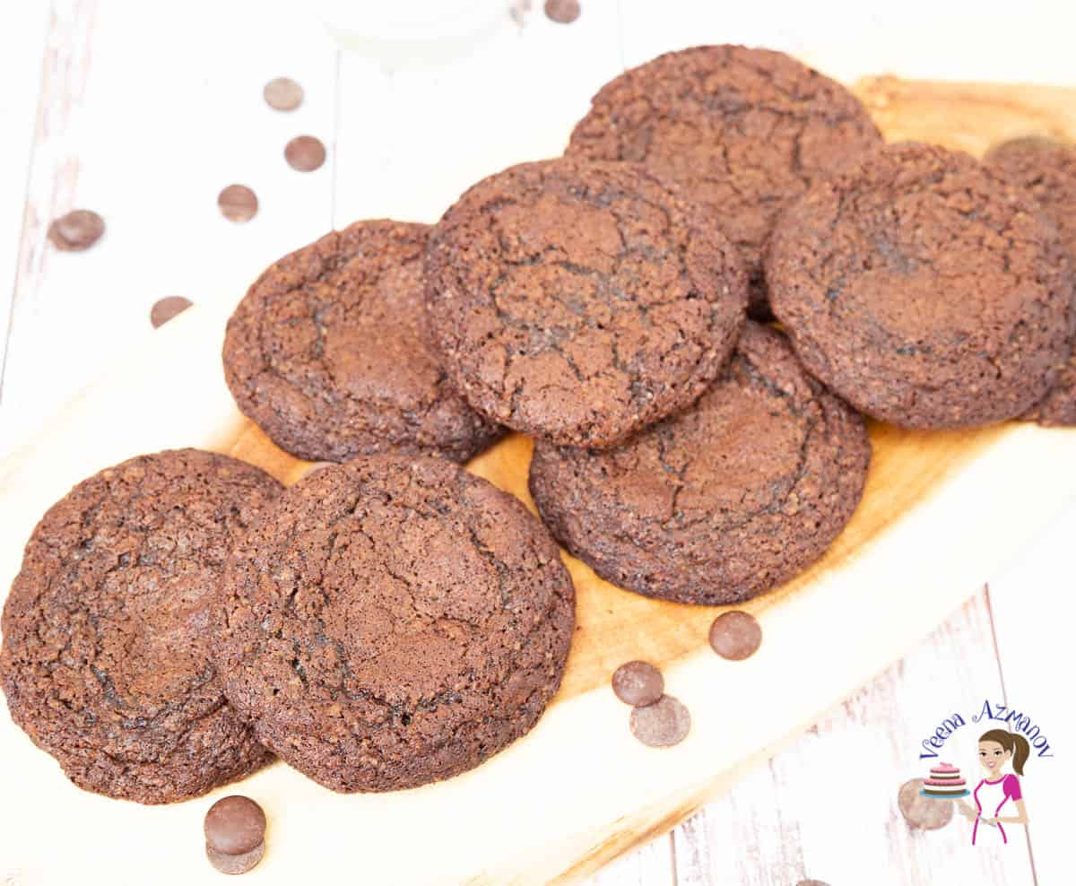 A stack of fudge chocolate cookies on a wooden tray.