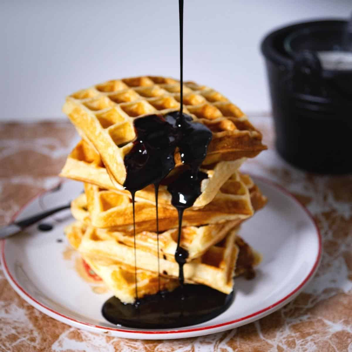 Waffles with pouring chocolate syrup.