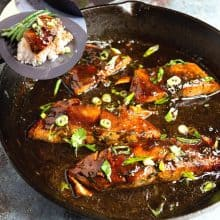 A skillet with salmon in balsamic glaze.