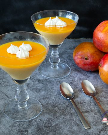 Two glasses with mango Panna cotta on a table.