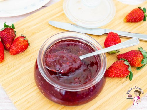 Strawberry jam in a jar with a spoon.
