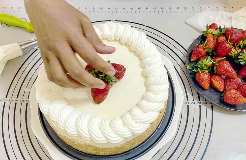 Garnish the cheesecake with seasonal fruits such as strawberries