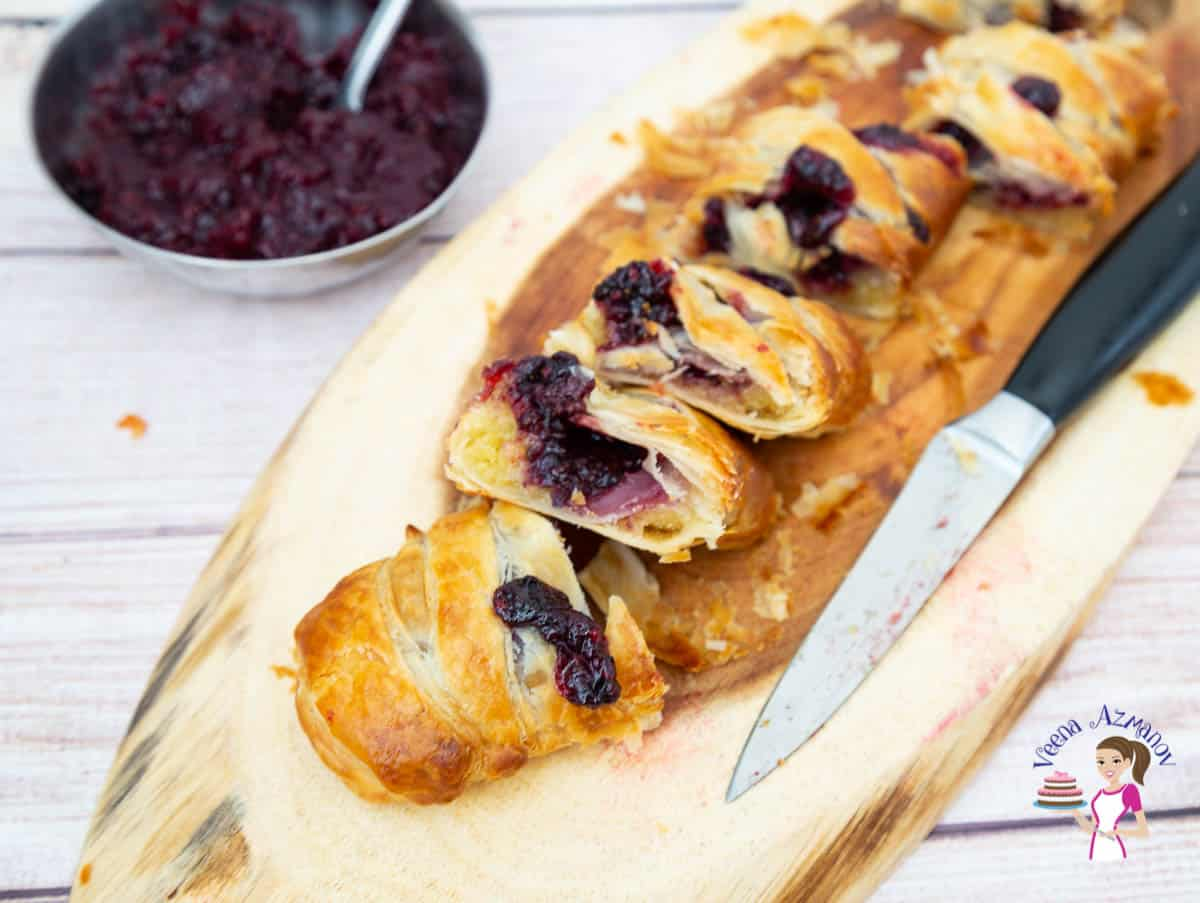 A sliced braided pastry with blackberries on a wooden board.