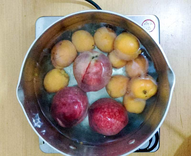Blanch the apricots and peaches in hot water