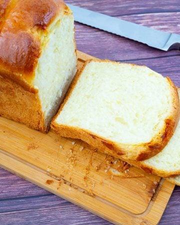 A sliced loaf of sandwich bread on a wooden cutting board.