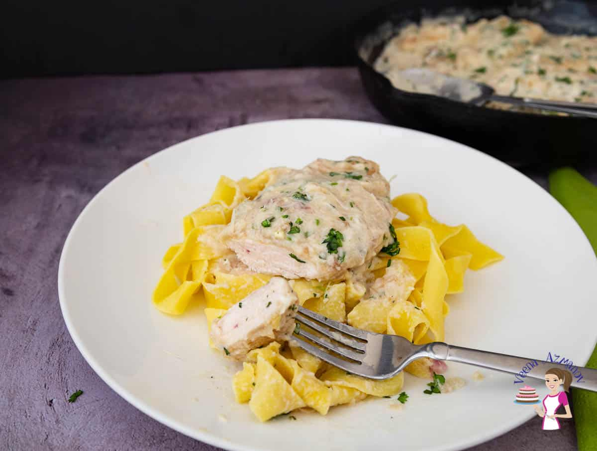 A plate of pasta with chicken in a white sauce.