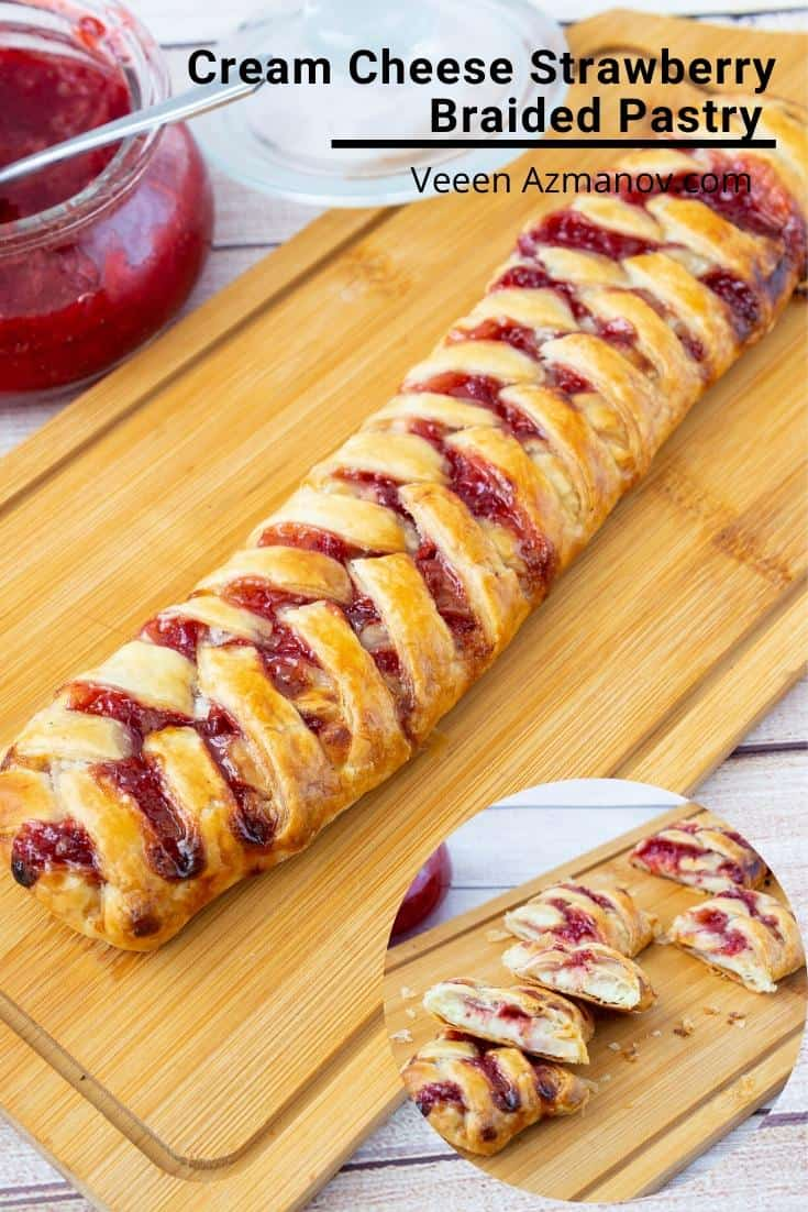 A braided puff pastry with strawberries on a cutting board.
