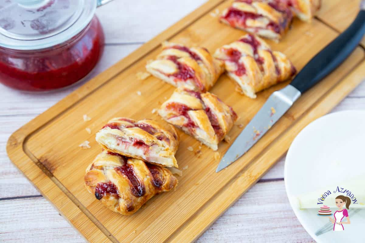 A sliced braided puff pastry with strawberries on a cutting board.