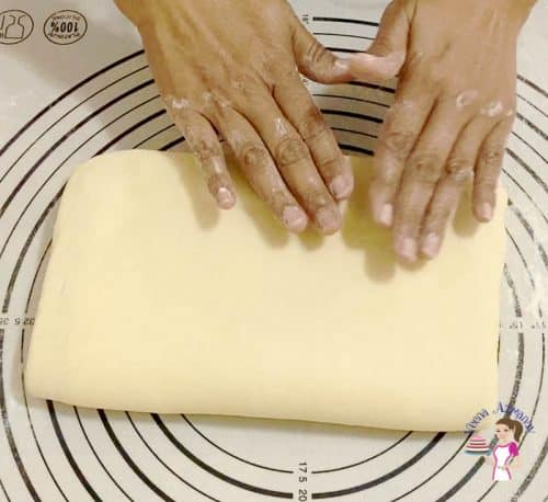 Fold and turn the dough for croissants three times