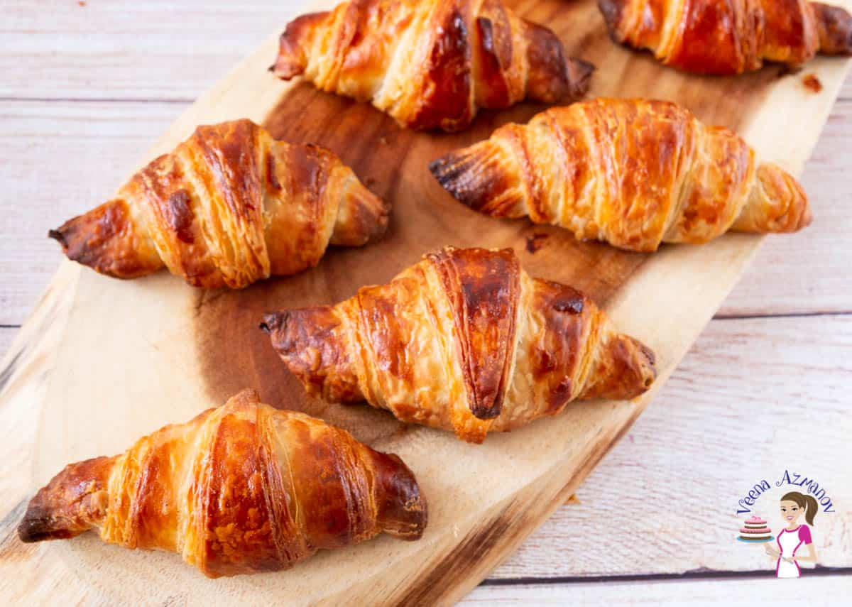 a wooden board with croissants