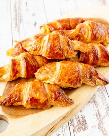 A stack of croissants on a wooden tray.