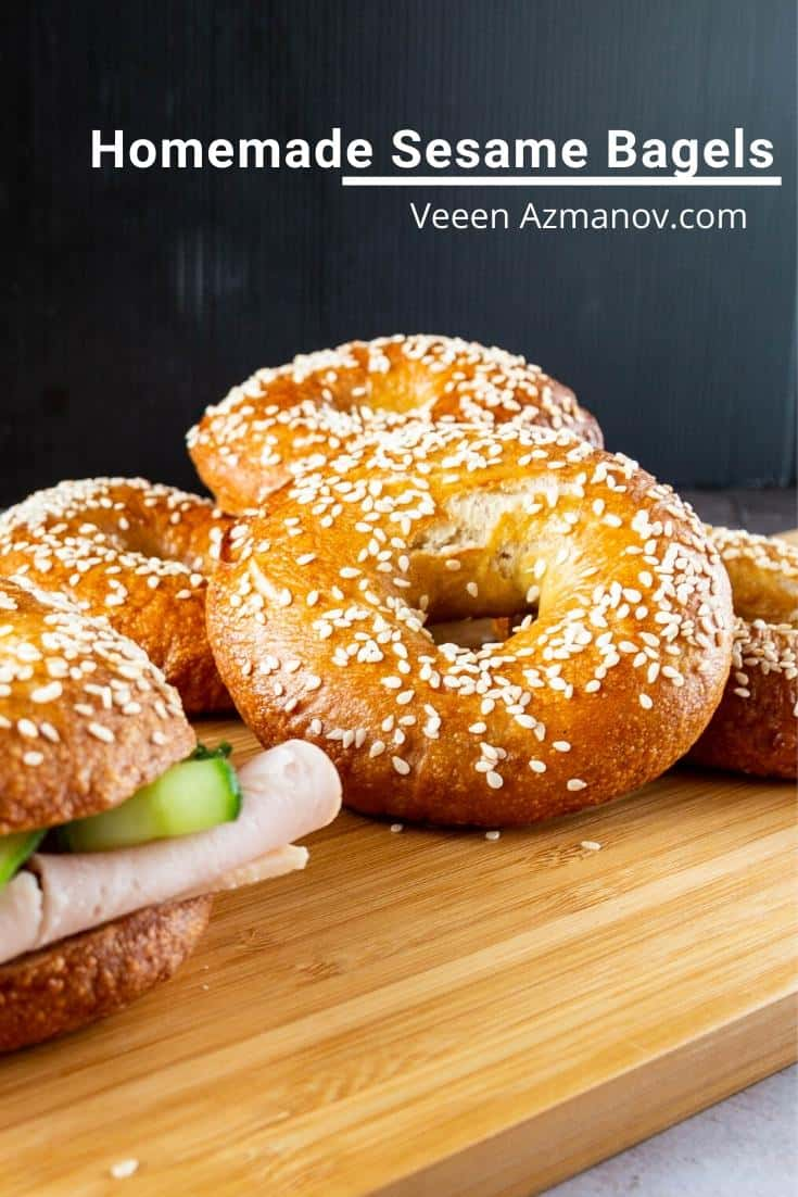 A stack of bagels on a wooden board.