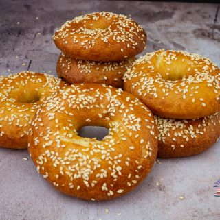 A stack bagels on a table.