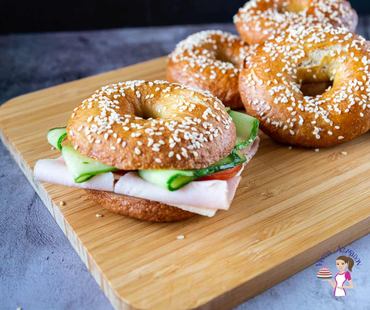 A bagel with pastrami and cucumber on a wooden board.