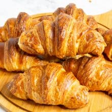 Stack of Croissants on a wooden board.