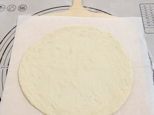 Roll the dough for pizza with white sauce