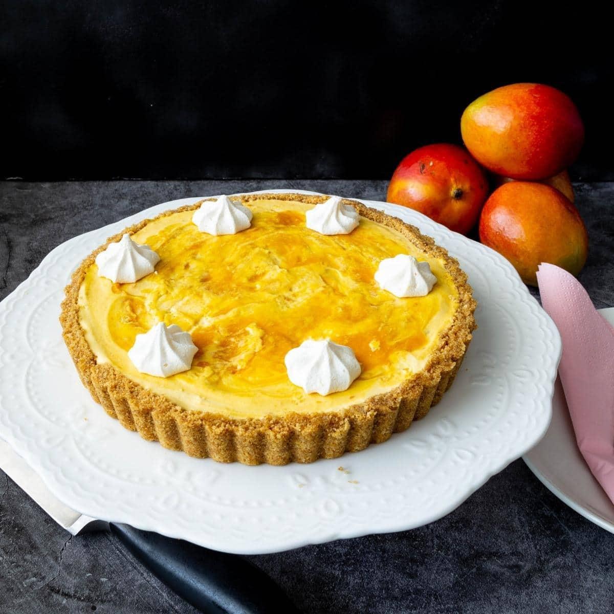 Mango cheesecake tart on a cake stand.