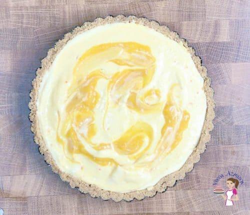 Create a swirl of the mango puree over the cheesecake tart.