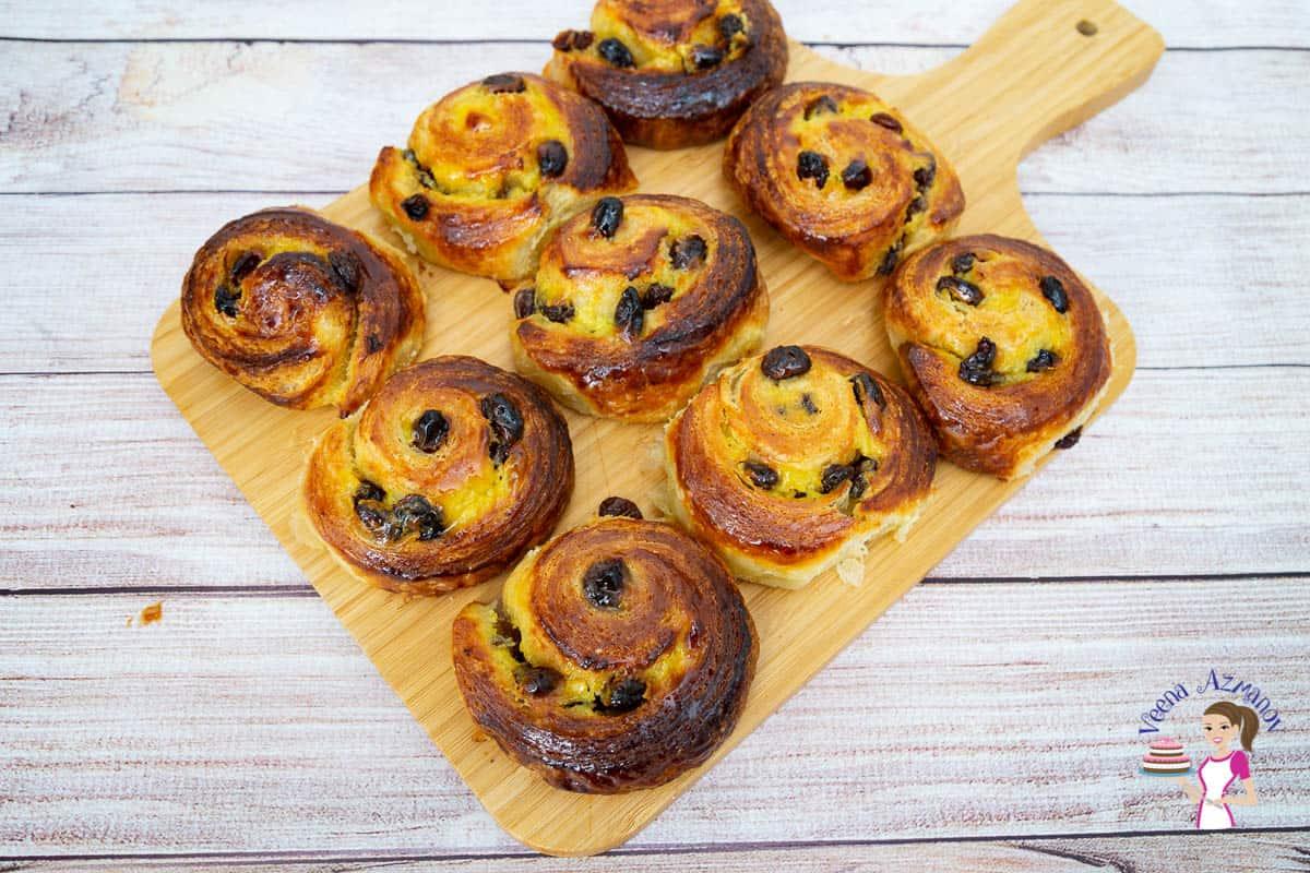 Raisin Danish pastry spirals on a wooden board.