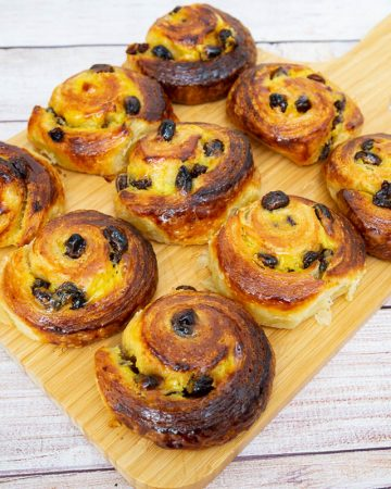 Danish pastry spirals with raisins on a wooden tray.