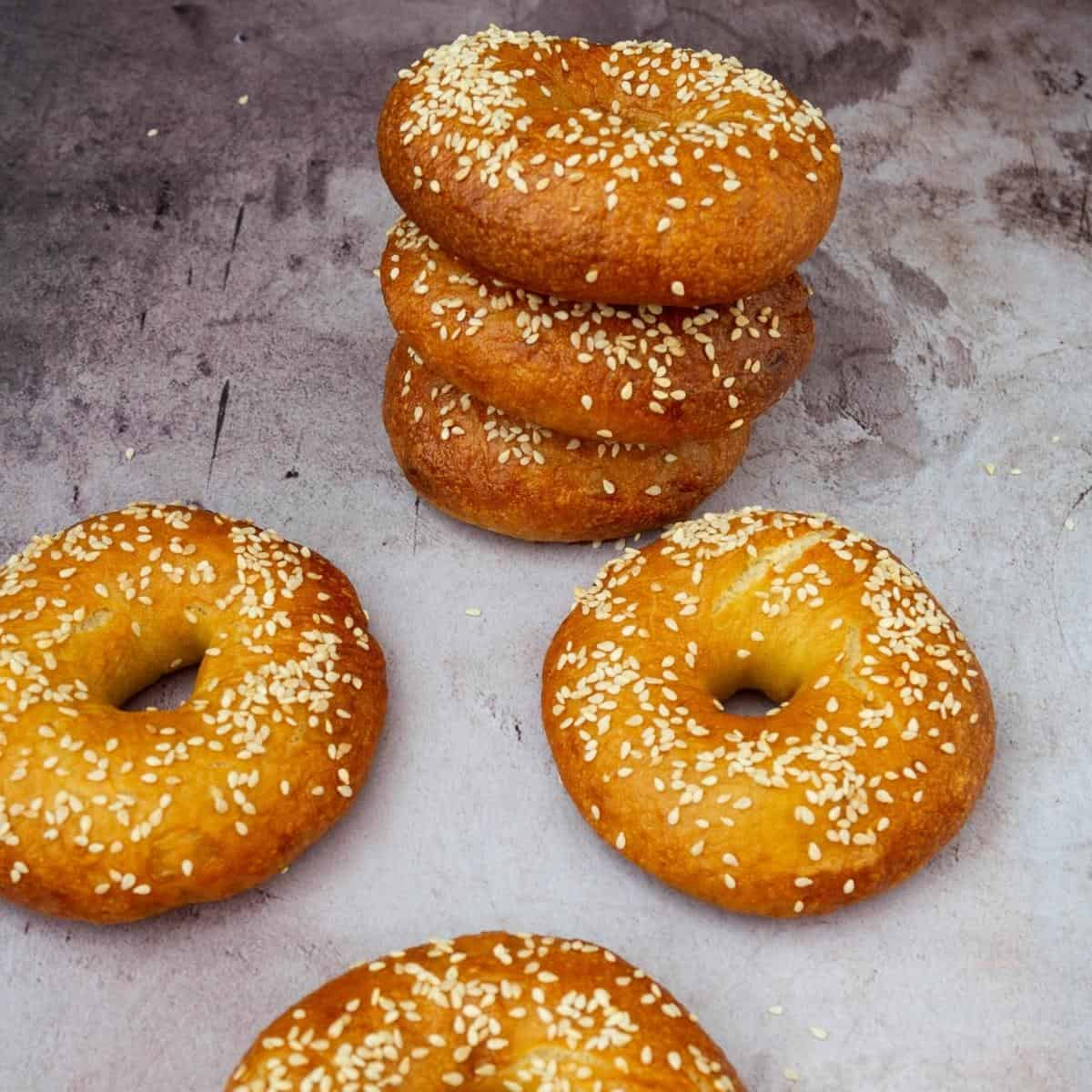 Bagels on a table topped with sesame seeds.