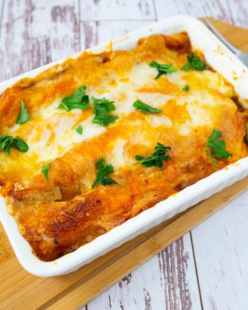 A baking dish with beef enchilada.