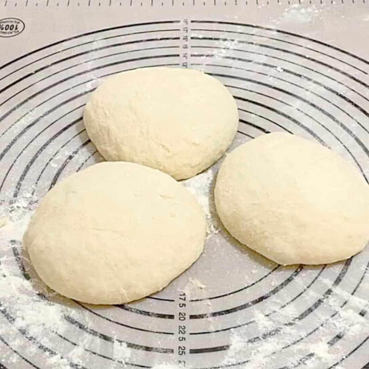Dividing the pizza dough into three.