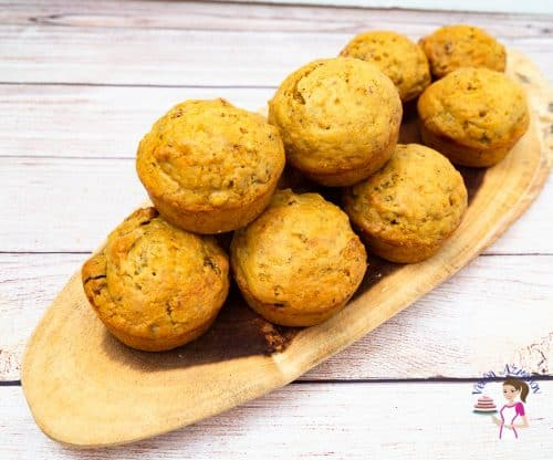 A stack of muffins on a wooden board.