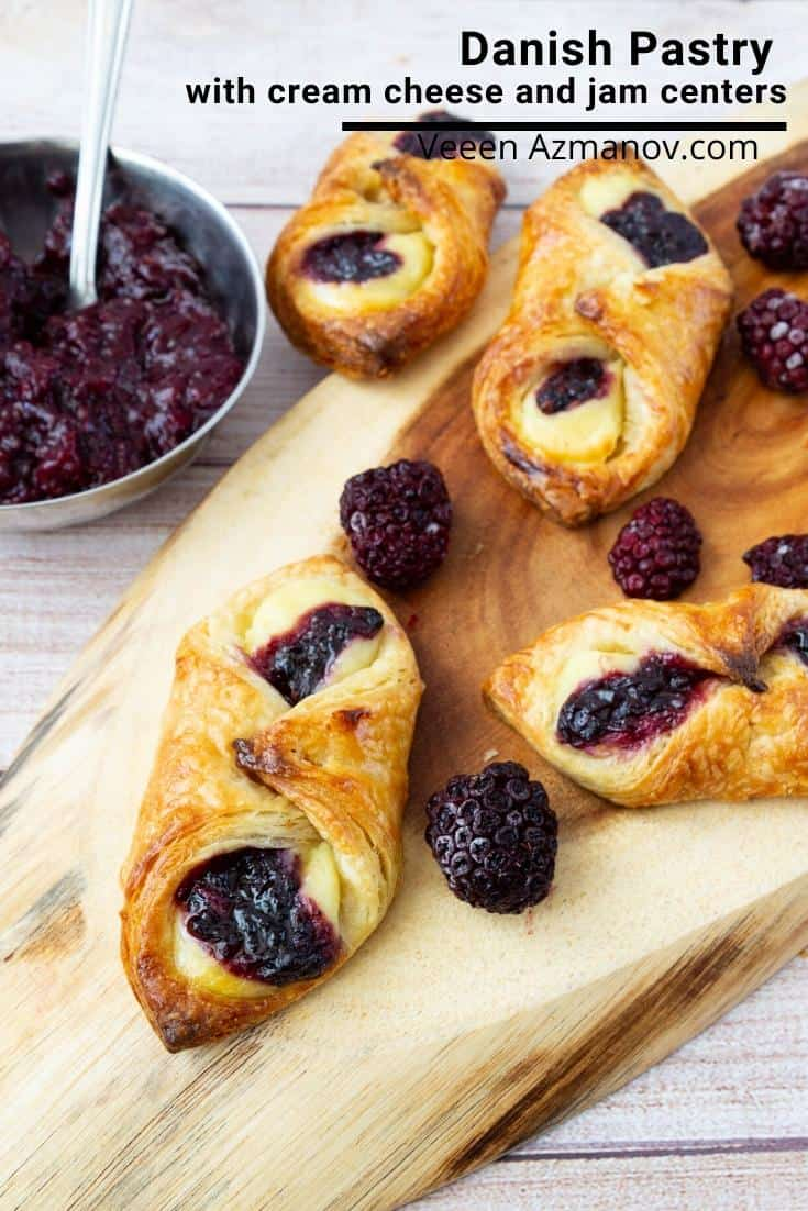 Danish pastry with berries on a wooden tray.