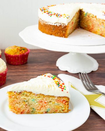 A slice of funfetti cake on a plate, with the remaining cake on a cake stand.