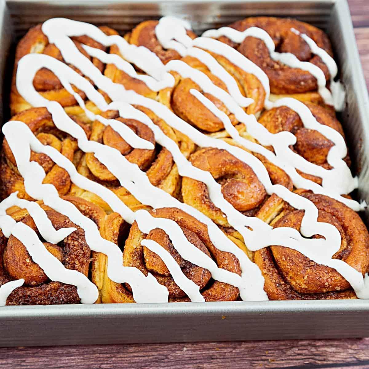A baking pan with glaze cinnamon rolls.