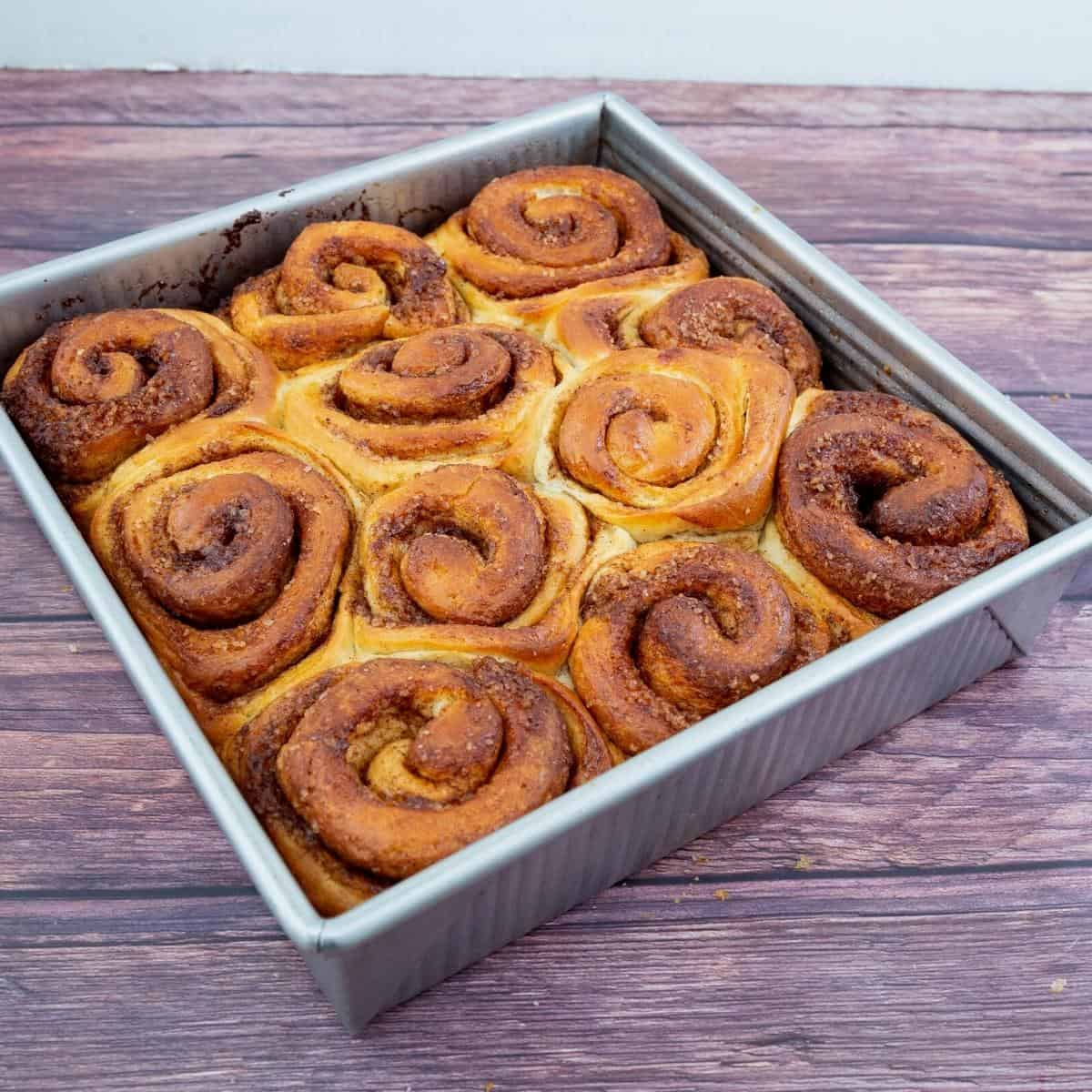 A baking tray with baked cinnamon rolls.