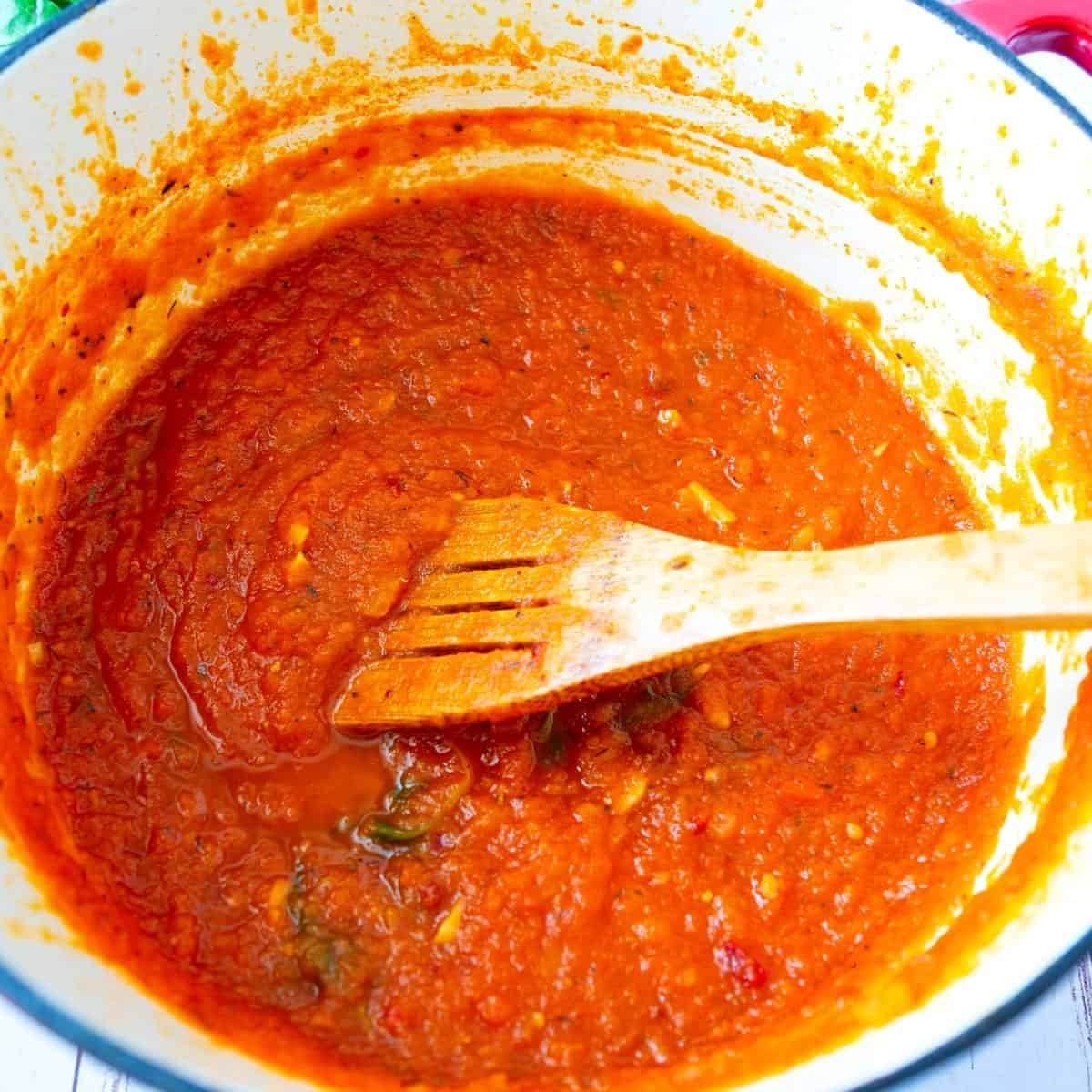 A Dutch oven pot with Marinara Sauce with Fresh Tomatoes.