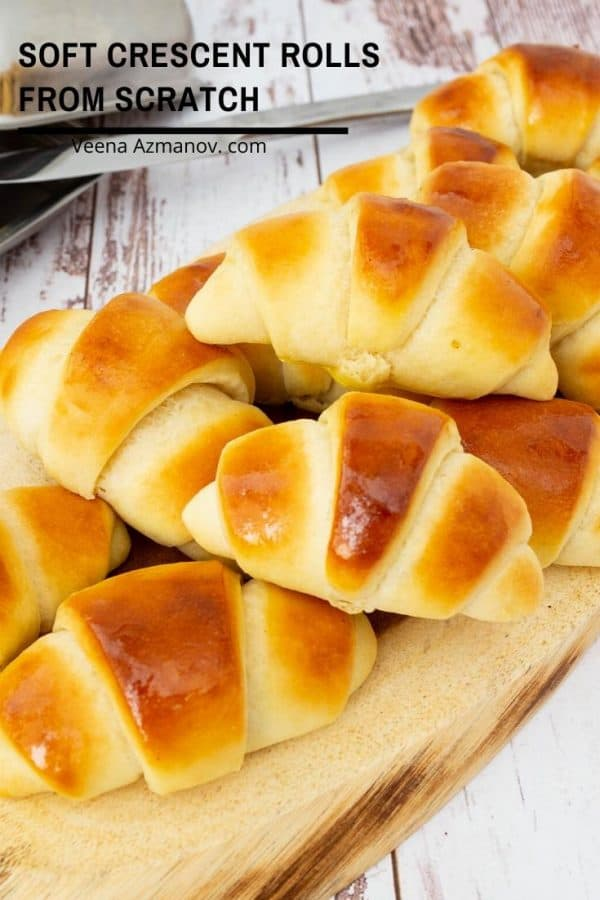 A stack of soft crescent rolls on a wooden tray.