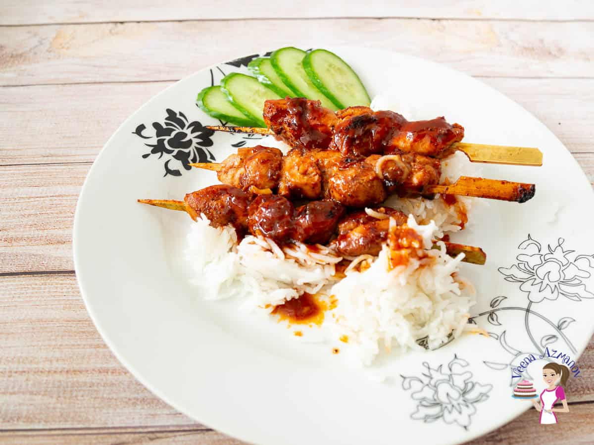 A plate with chicken skewers, rice and cucumbers.