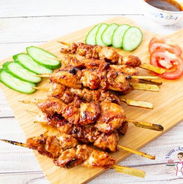 A stack of chicken skewers on a wooden board with sliced cucumbers and Tomato.