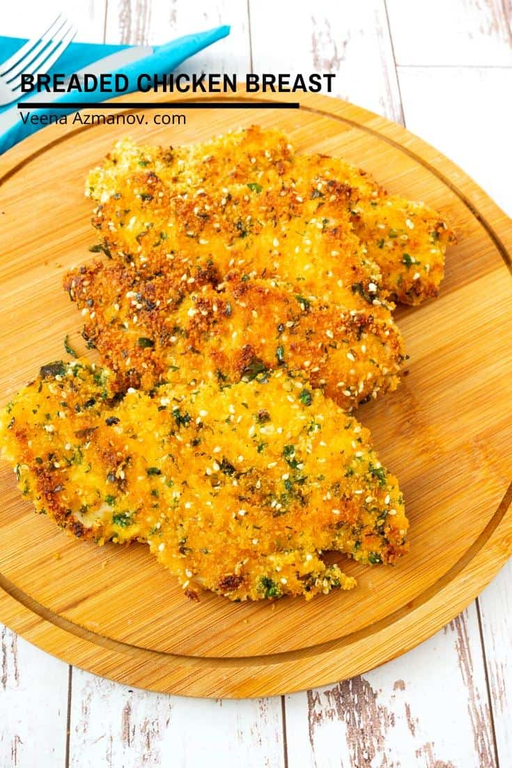 Three breaded chicken breasts on a round wooden board.