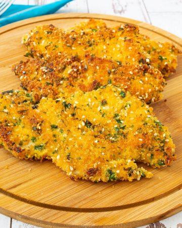 Pan fried breaded chicken breast on a wooden board.