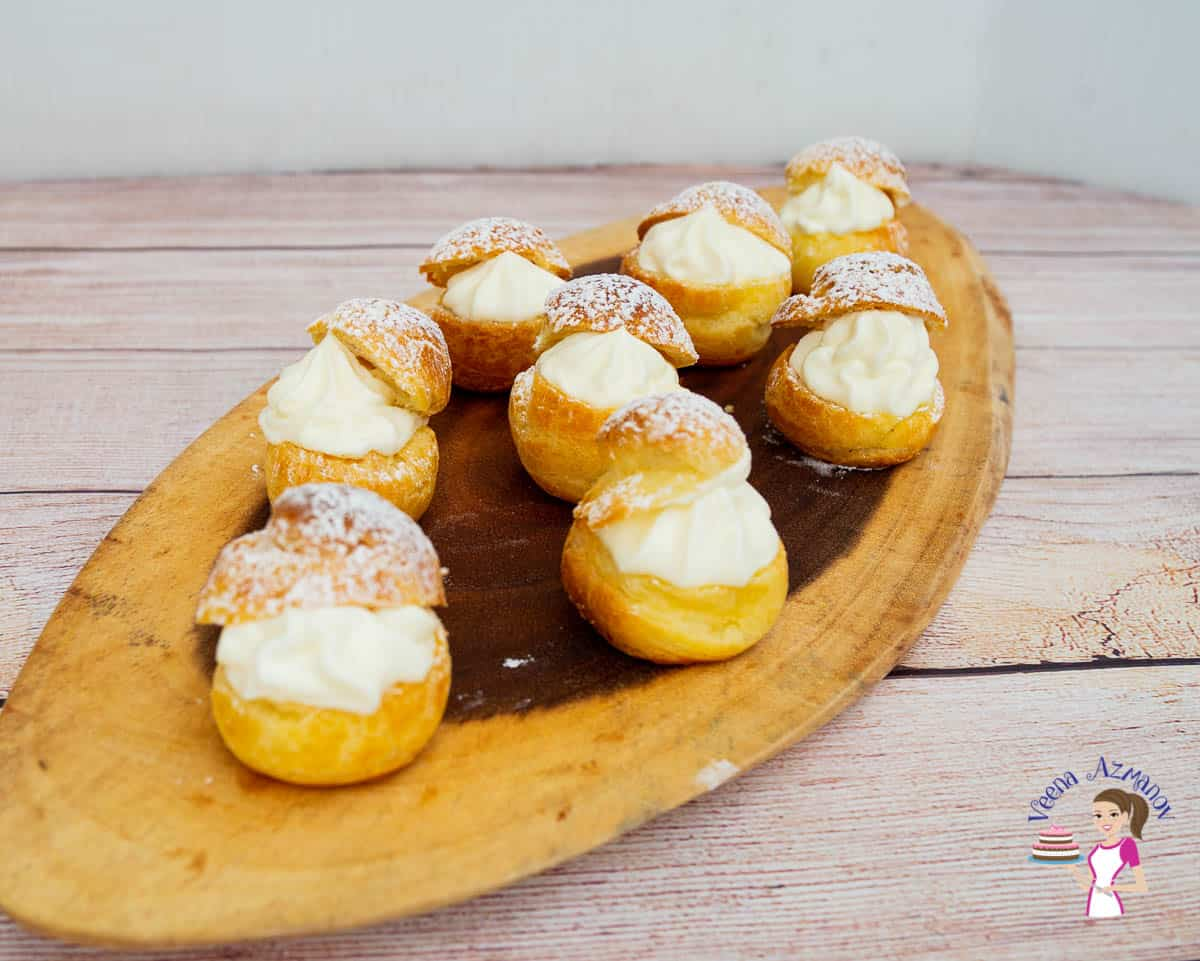Cream puffs on a wooden tray.